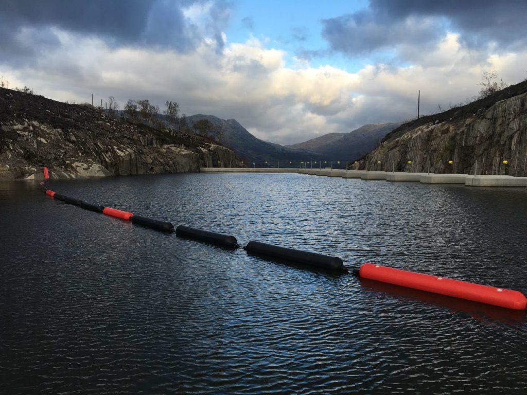 Foto viser singel åpen barriere i front av det nye overløpet ved dam Deg. Barrieren er på drøye hundre meter og er forankret mot to landfester og syv moringsfester.