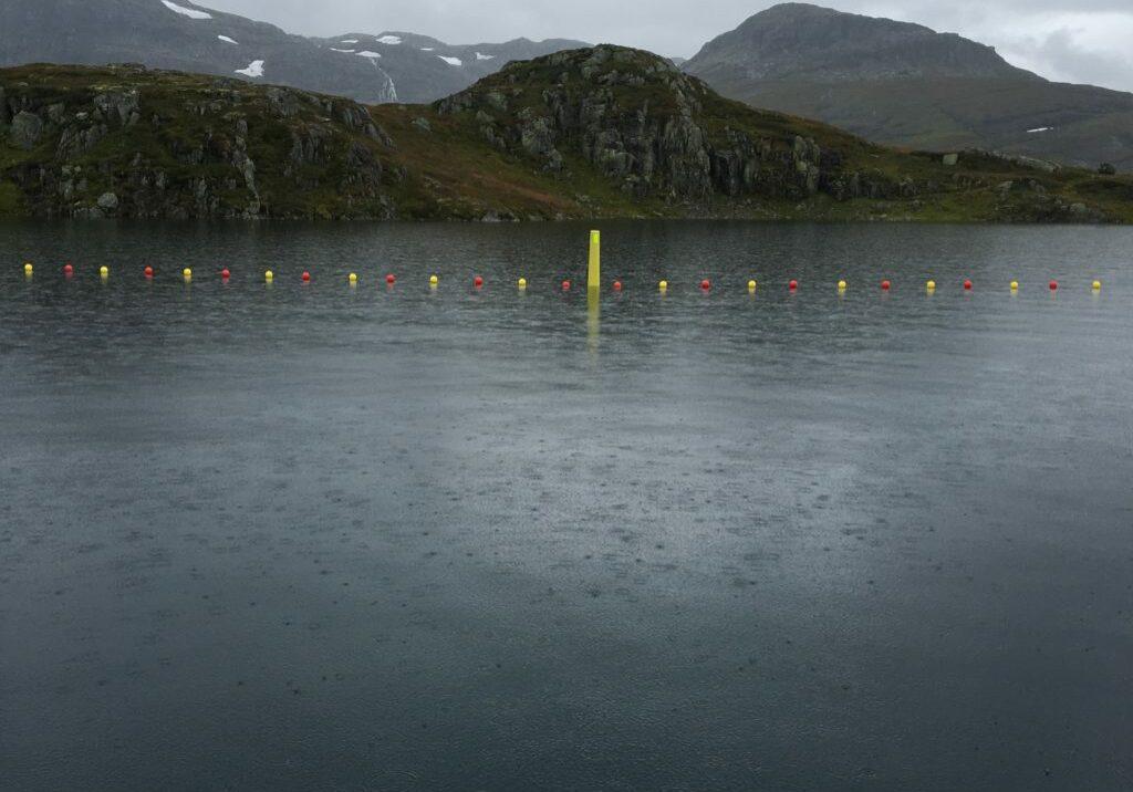 Foto viser installasjonen i front av dypvannsinntaket på Ståvatn. Haukeliseter, Norges mest besøkte turisthytte, ligger på andre siden av vannet. Dermed er det stor ferdsel av turfolk i området både sommer og vinter.